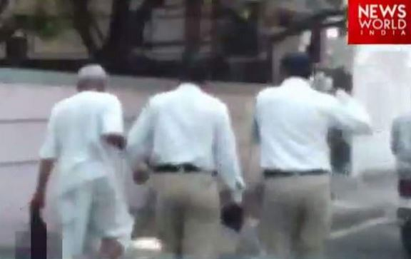 Above is a still picture from the video. In the picture, police officers can be seen marching the 60-year-old to the police station.